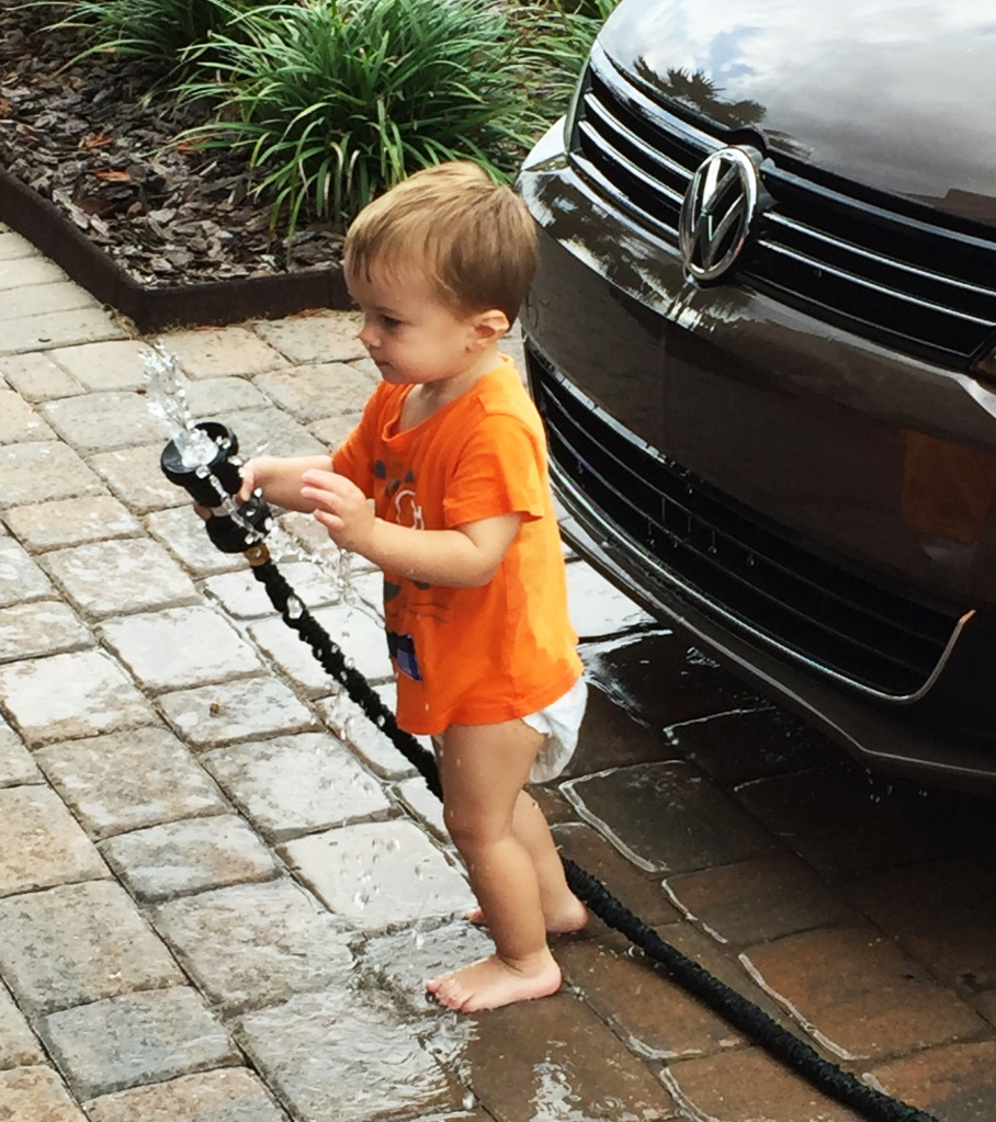 Helping Daddy wash the car while washing himself apparently.